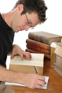 Young malelaw student taking notes from a law book at the law library