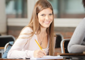 Portrait of beautiful college student sitting at desk in classro