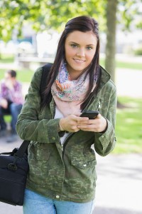 Portrait of a college girl text messaging with blurred students