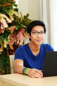 Young asian student studying at laptop