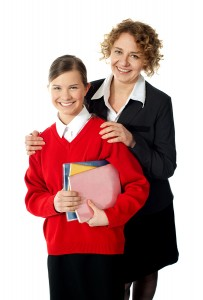 Smiling female tutor with high school girl student carrying notebooks