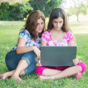 Hispanic mom and teen studying on laptop in park