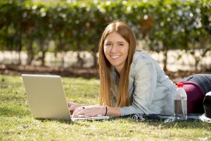 Female college student studying outdoors on laptop