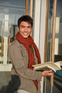 A portrait of smiling college student holding book at campus