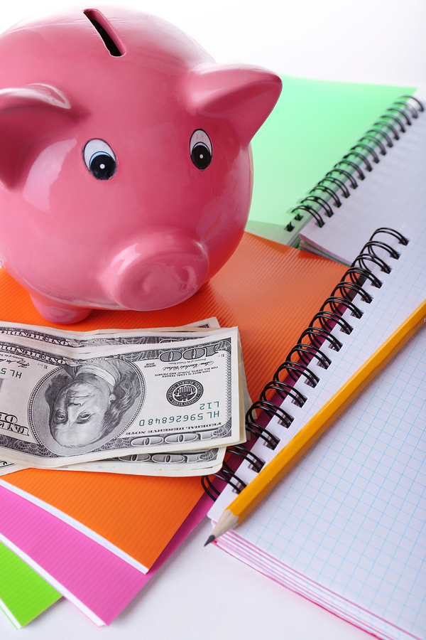 Piggy bank, cash and notebooks denoting paying for college
