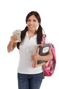 Young female college student holding cash from her student loan to pay for college