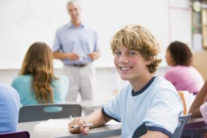 Male Student With Other Students In Classroom